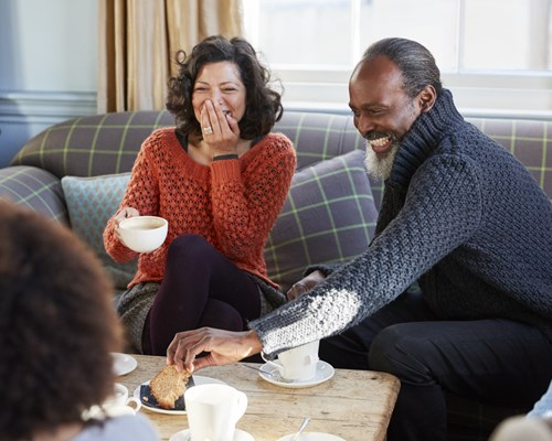 Couple laughing having tea and cake