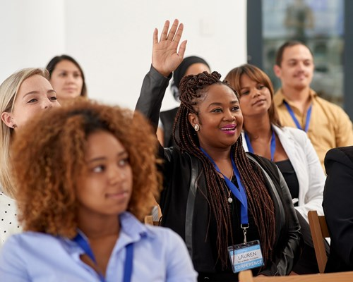 Woman raising hand in a meeting